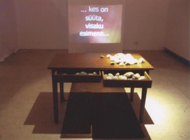 """""""KES SÜÜTA, VISAKU ESIMENE KIVI..."""" 2003 installatsioon: laud, kivid, video <br/> """"WHO IS INNOCENT, ...."""" 2003 installation: table, stones, video"""